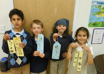Displaying their laminated floral bookmarks from spring flowers they collected.